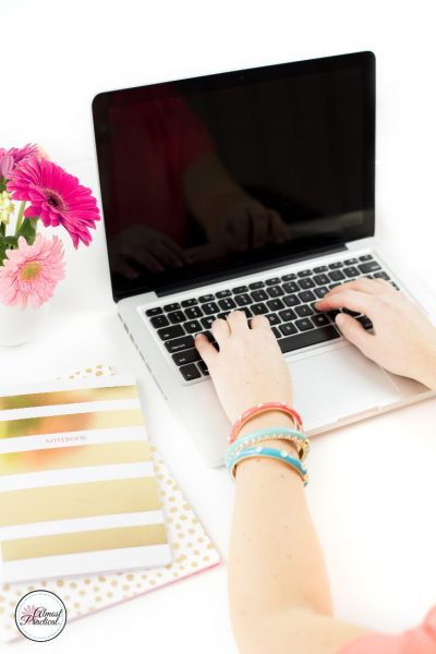 Woman typing on laptop with pink flowers close by and pretty notebooks.
