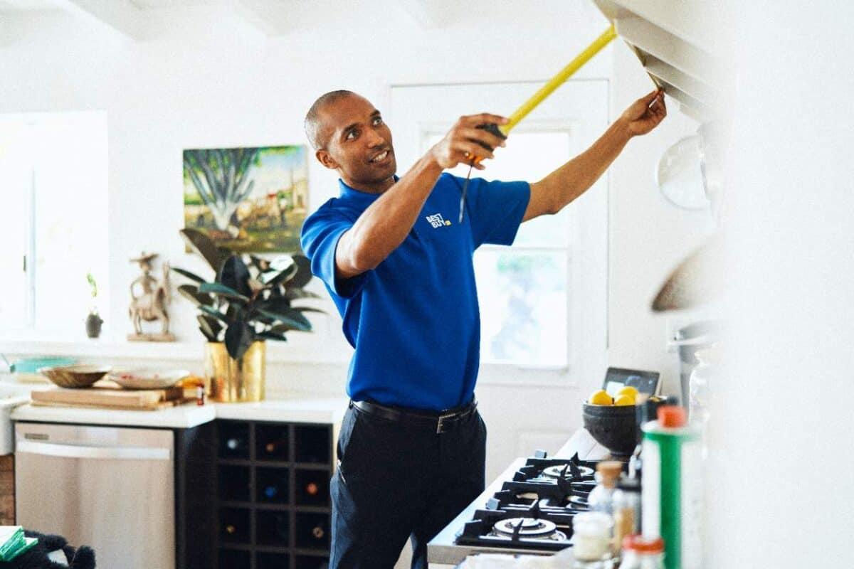 Best Buy In Home Advisor measuring a range hood in customers home.