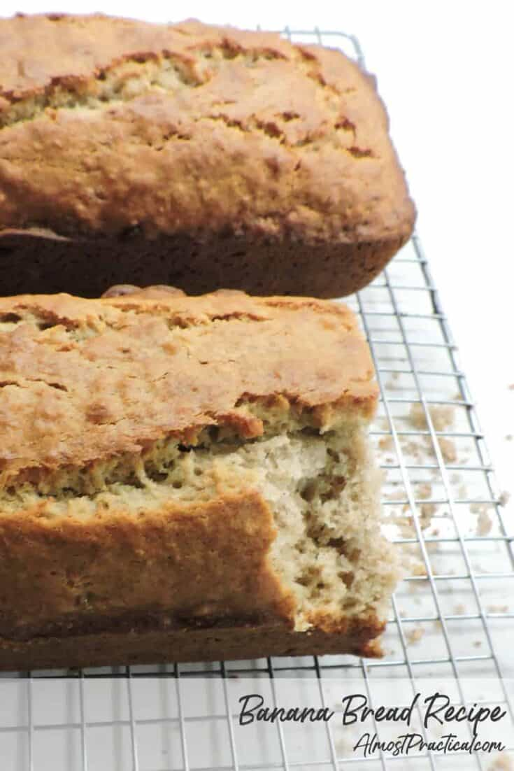 2 loaves of banana bread on a cooling rack with a slice taken and crumbs underneath