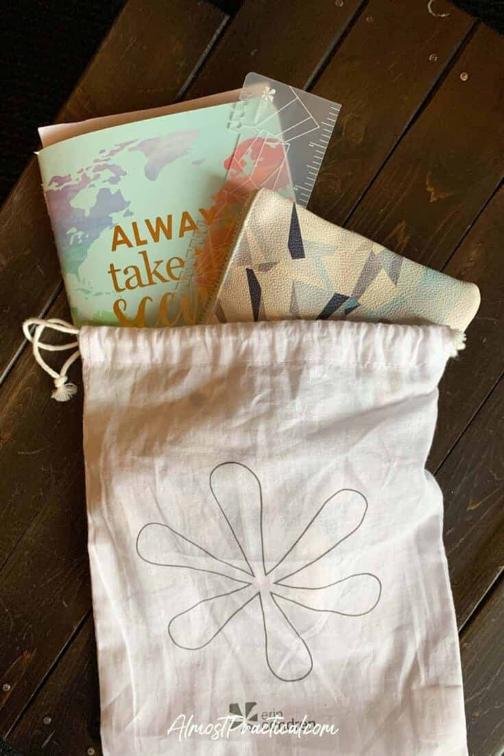 Erin Condren travel journal and planner accessories in a cream colored drawstring bag with Erin Condren logo on the front.
