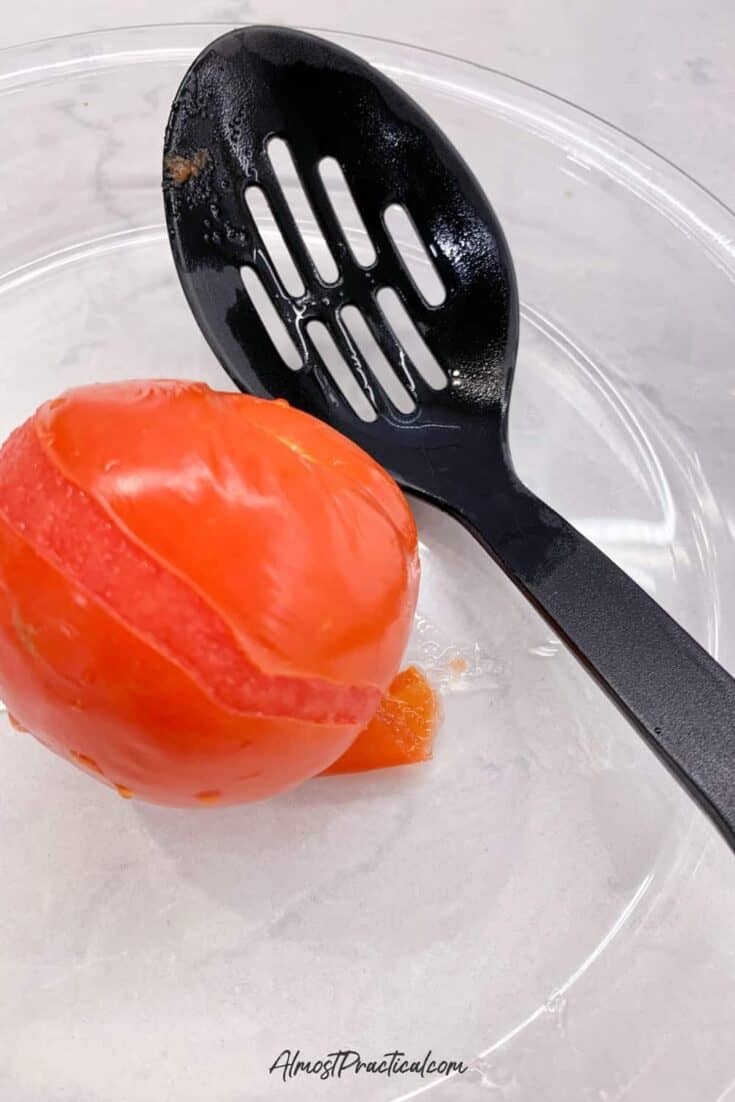 one blanched tomato in a glass pie plate next to a slotted spoon.