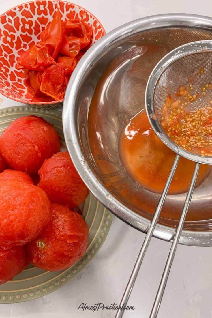 a stainless steel fine mesh strainer over a stainless steel mixing bowl that is being used to strain tomato seeds.