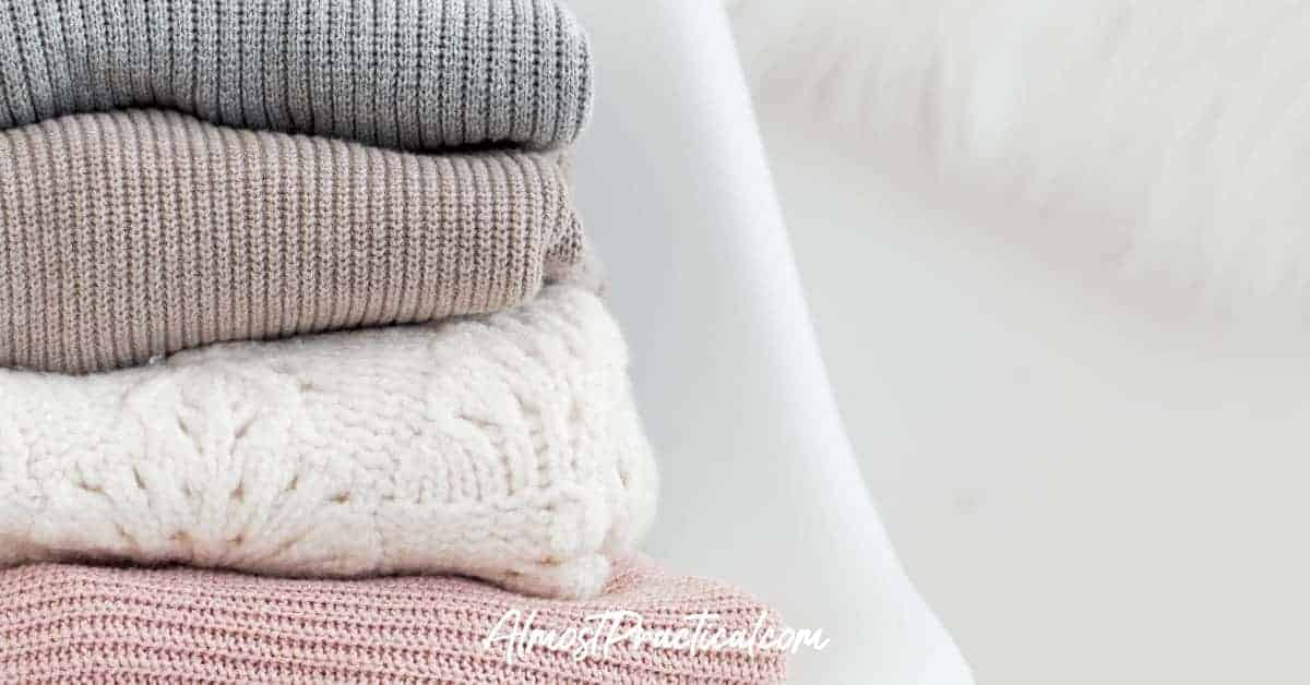 stack of folded sweaters on a chair
