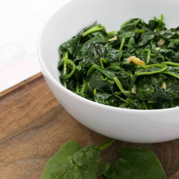 bowl of wilted spinach with garlic side dish