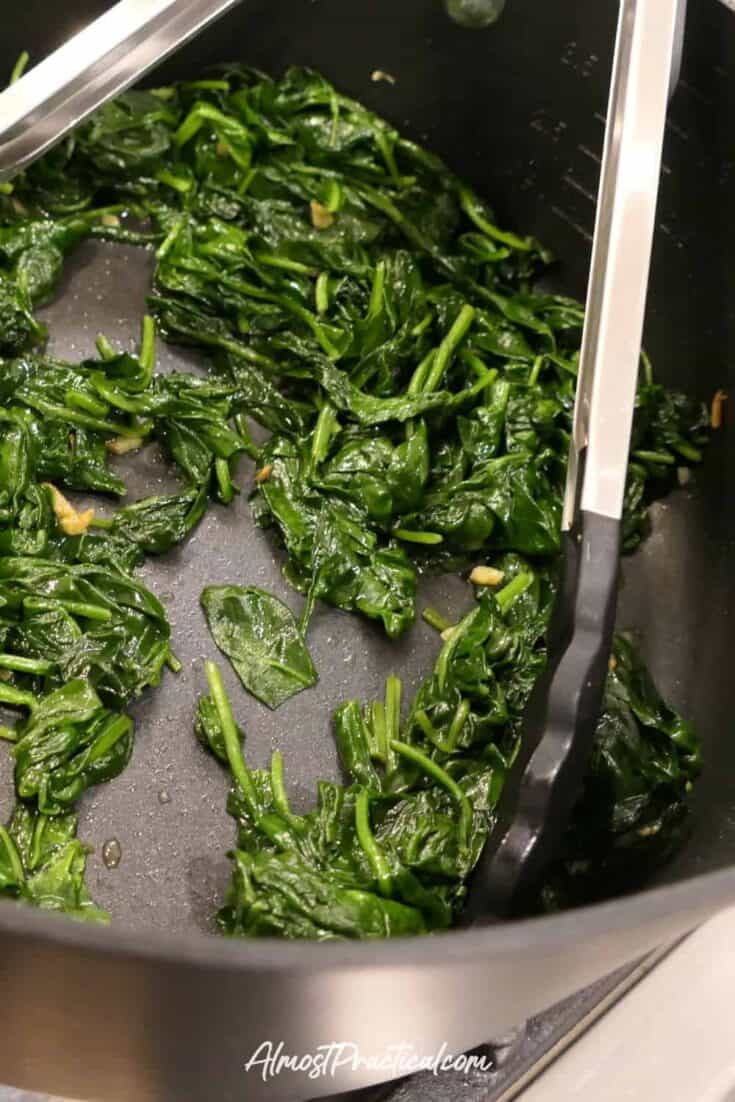 Photo showing wilted spinach with garlic in a nonstick pan with long handled silicone tipped tongs.