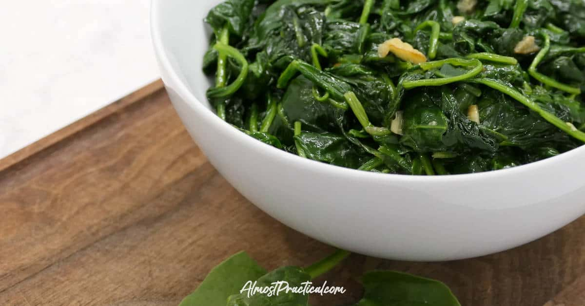 Wilted spinach and garlic in a serving bowl.