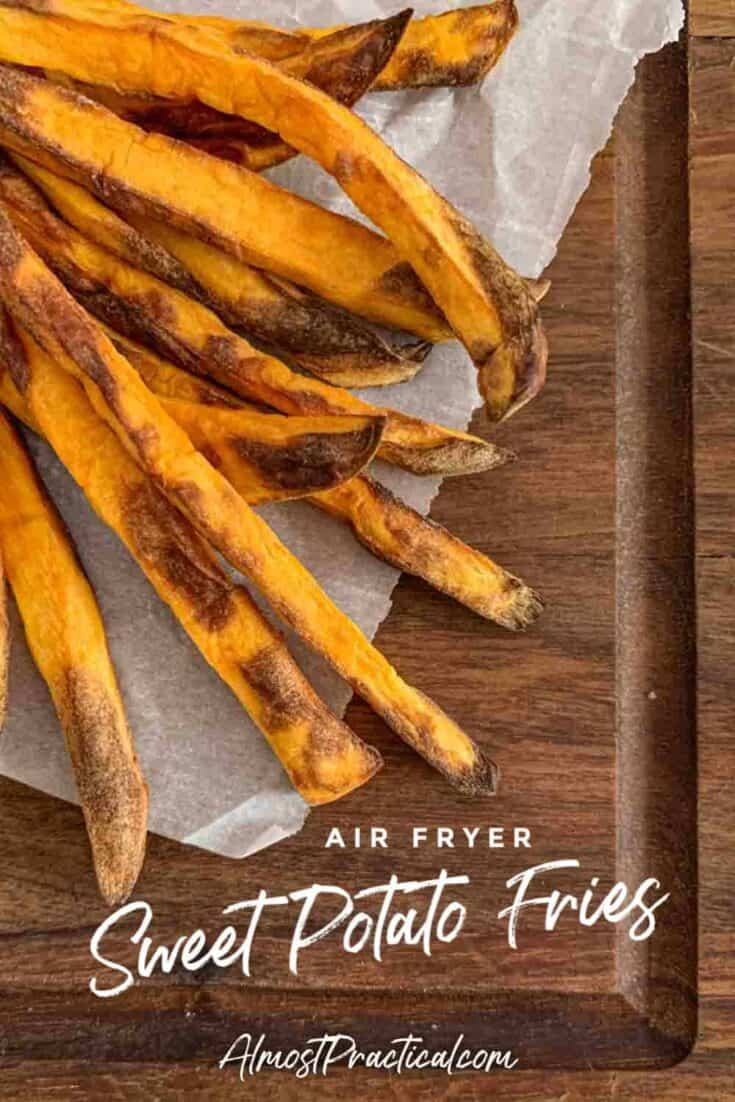Sweet potato fries on parchment paper on a walnut cutting board.