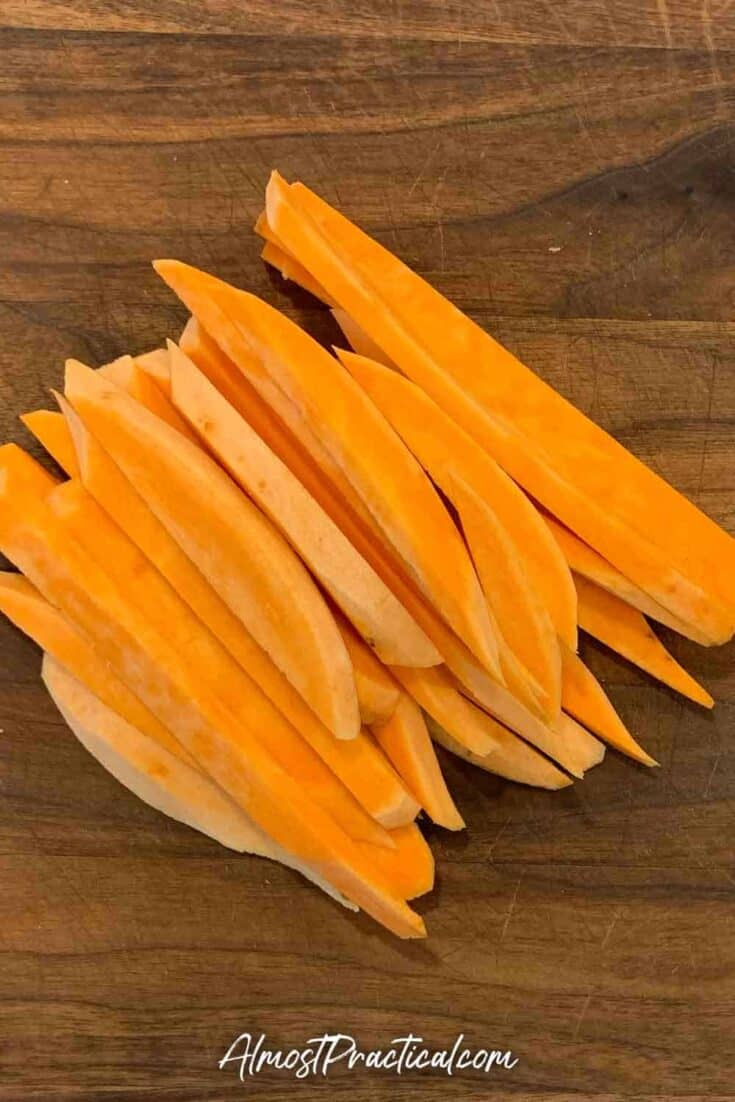 raw sweet potatoes cut into fries on a cutting board
