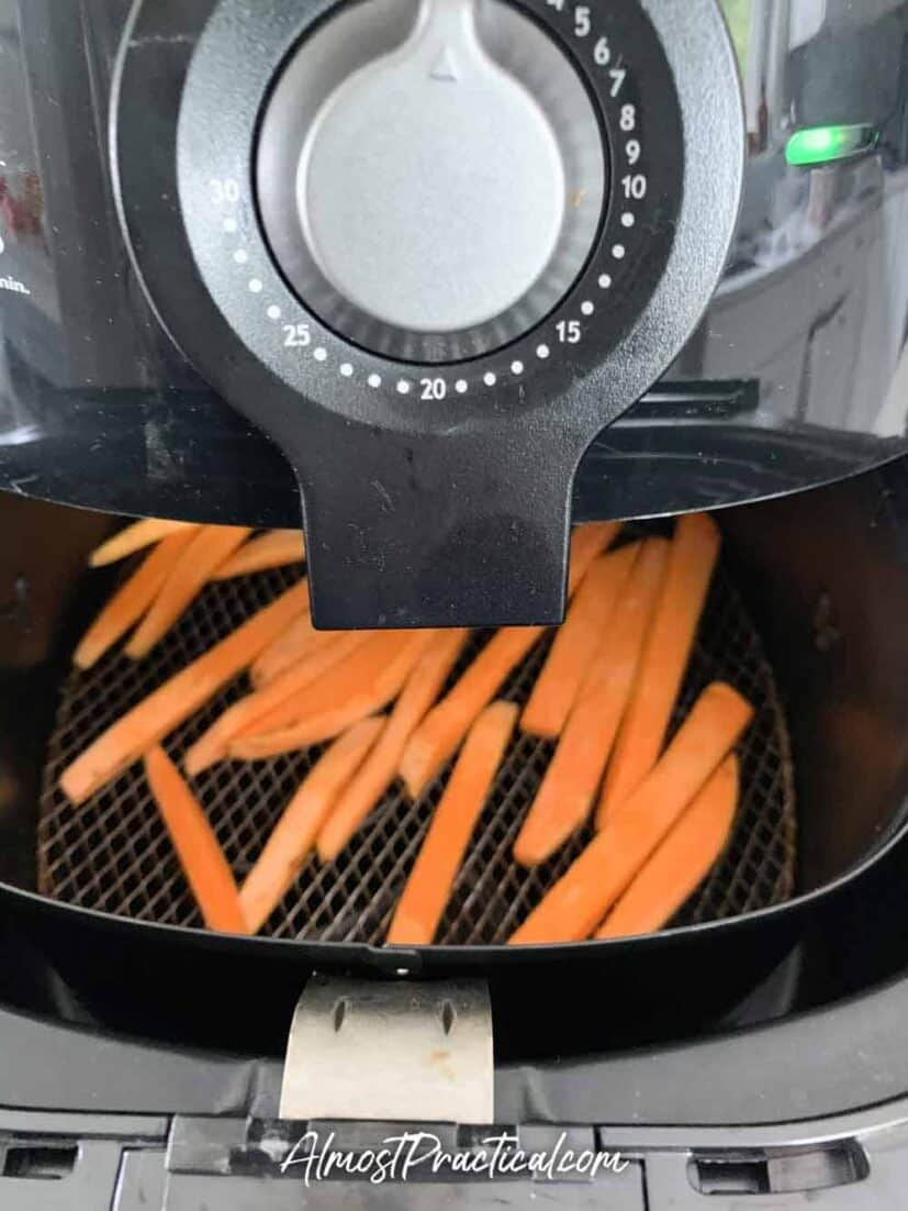 Air fryer with basket half open showing how sweet potato fries inside should be spaced for even cooking.