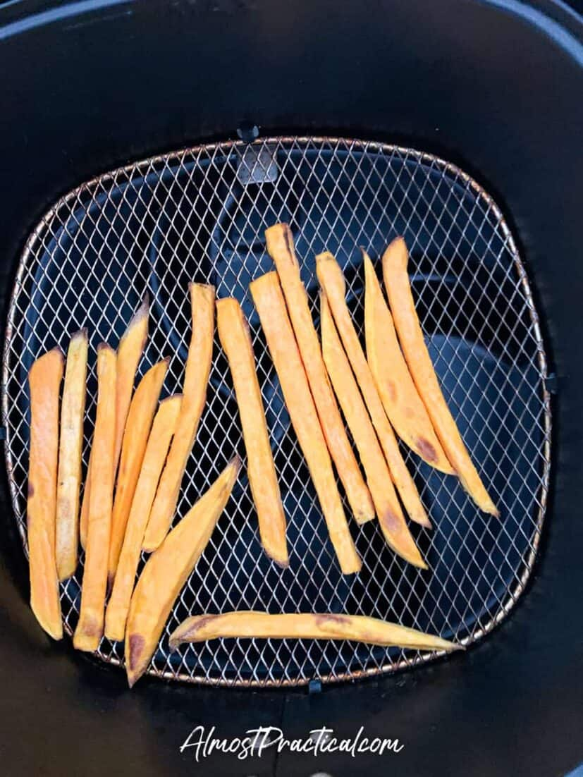 Sweet potato fries in air fryer basket at 3 minute mark.