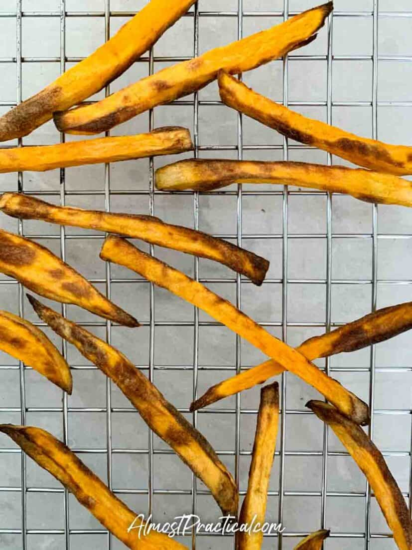 Cooked sweet potato fries on a cooling rack.