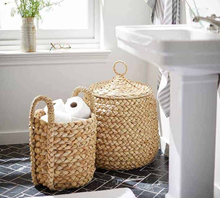 Pottery Barn baskets in bathroom holding toilet paper rolls.