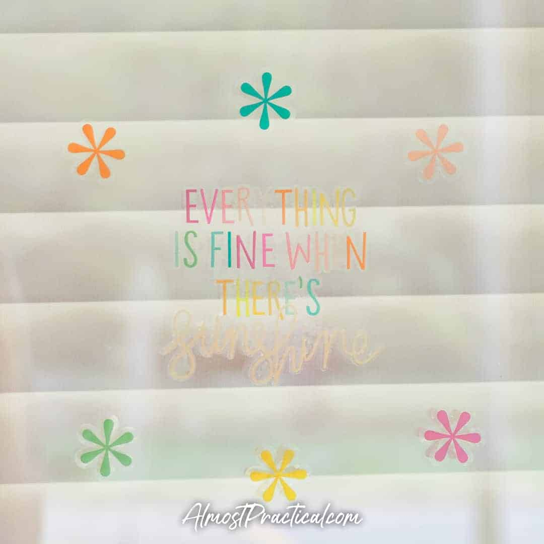"Erin Condren vinyl cling stickers applied to a window - the quote pictured is ""Everything is fine with Sunshine"""