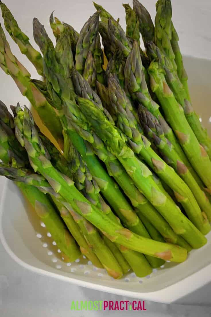 raw asparagus in a strainer