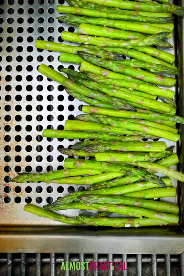 Asparagus in grill topper pan with holes cooking on the grill.