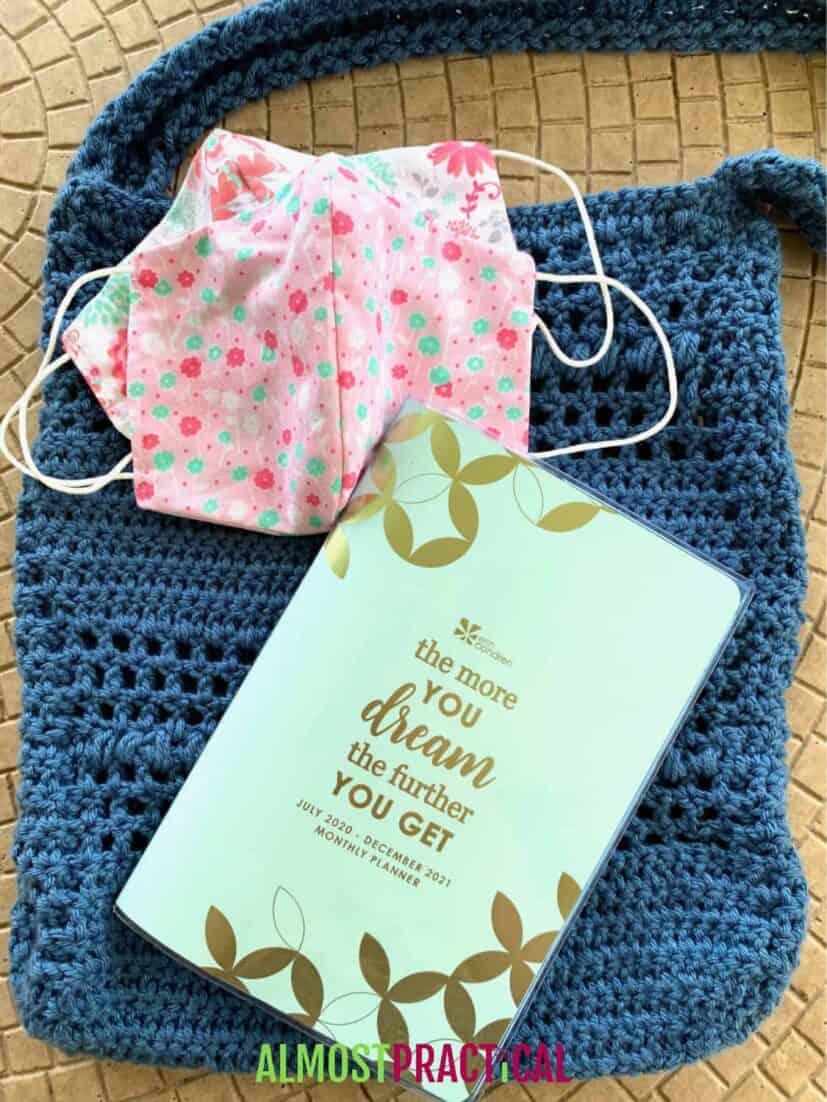 Notebook on top of crochet purse and handmade facemasks.