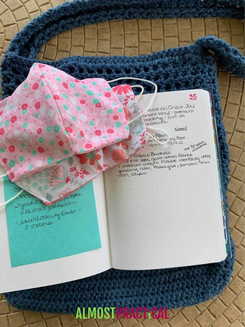 dot grid notebook with crochet purse underneath and cloth face masks on top
