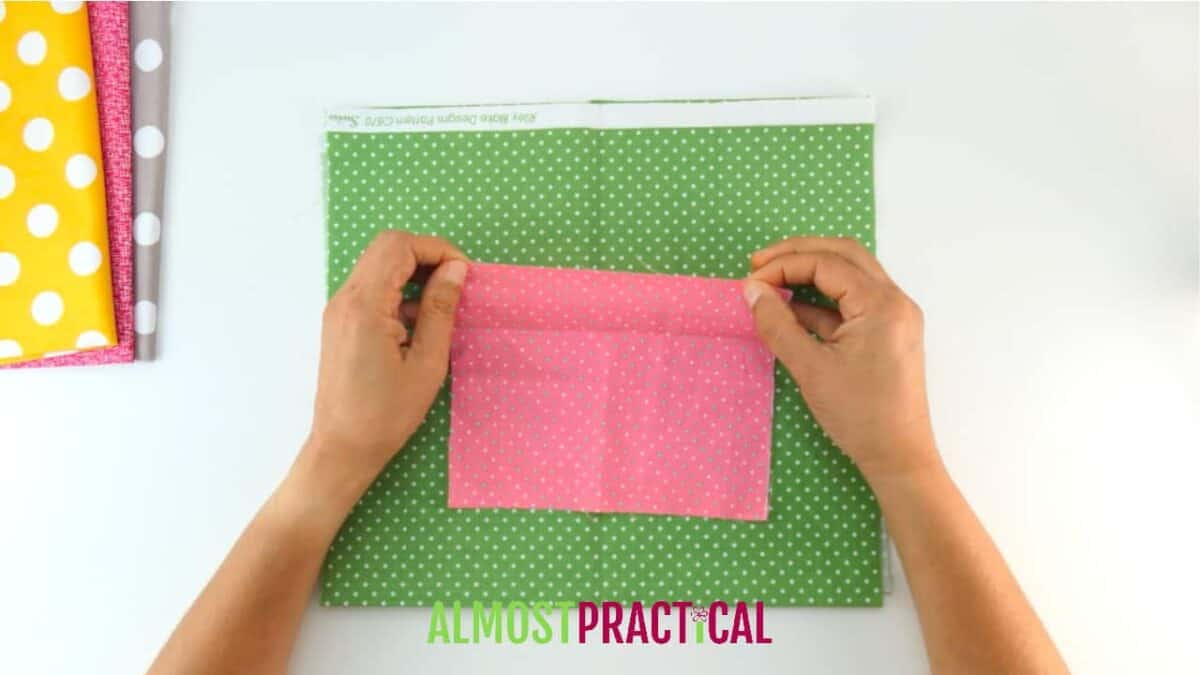 small scrap of pink fabric on top of green fabric