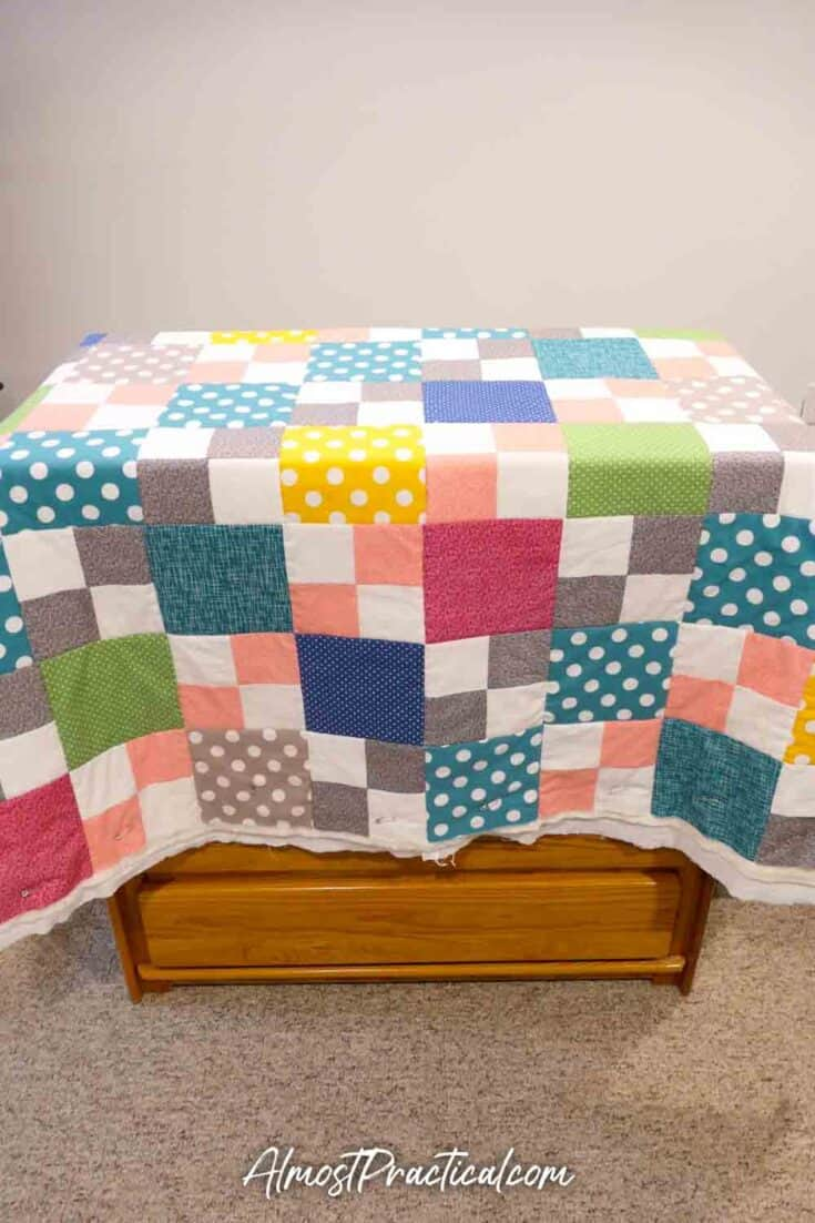 quilt draped over a chest of drawers