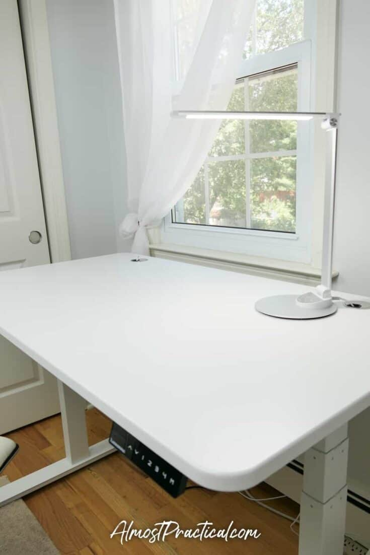 White standing desk with desk lamp on top.