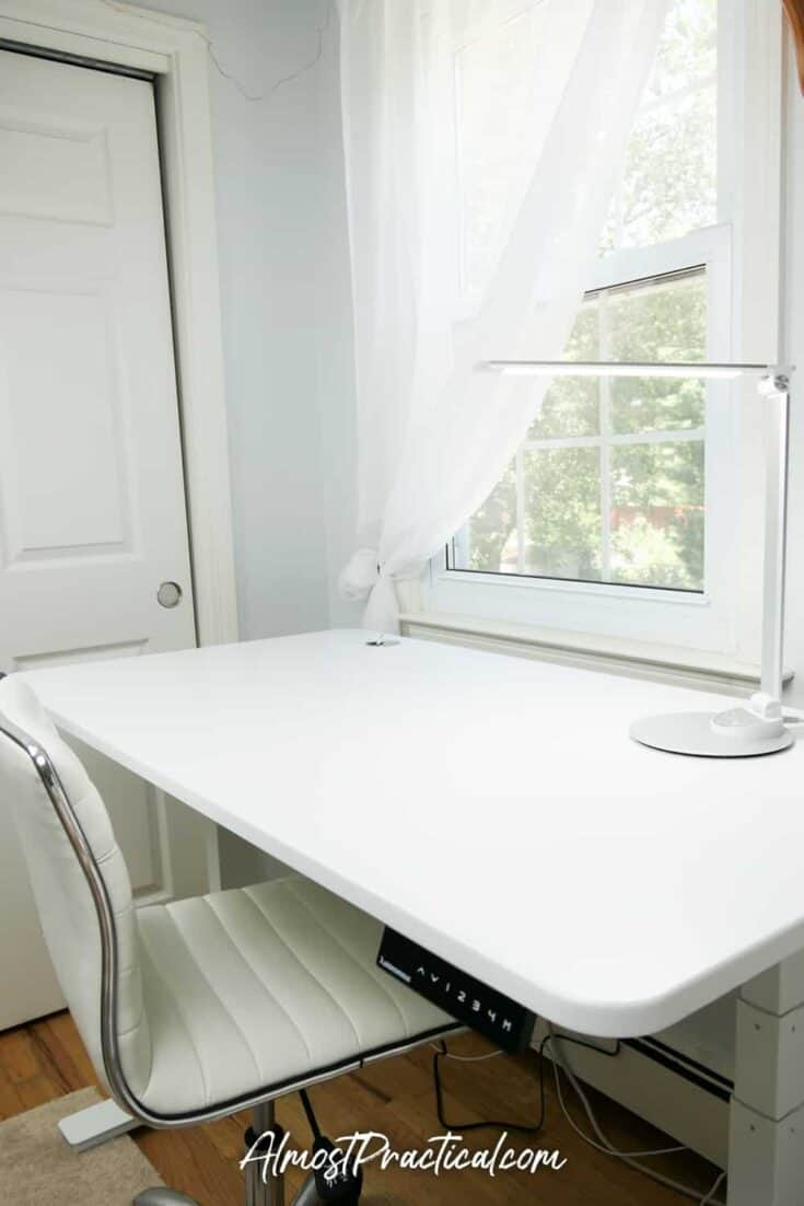 White standing desk with lamp on top.