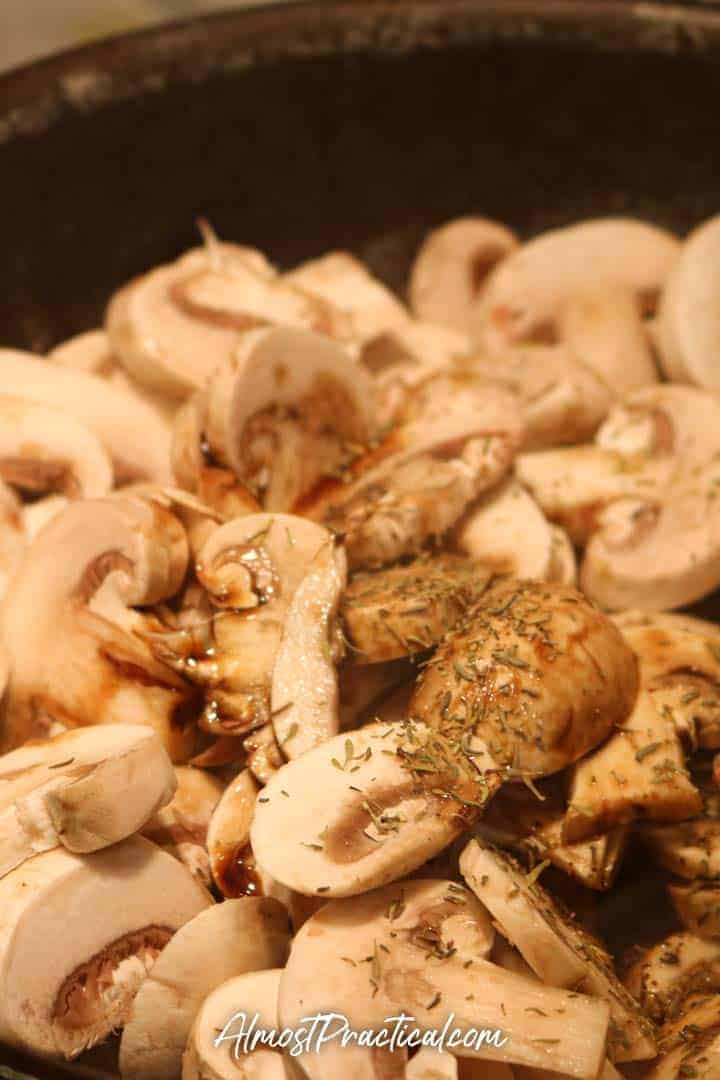 sliced mushrooms in a pan with thyme
