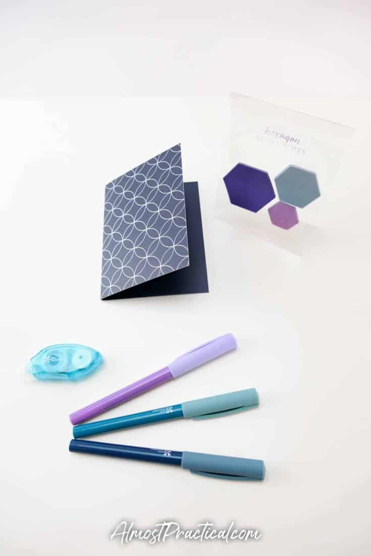 hexagon shaped sticky notes, a small tape dispenser and 3 pens.