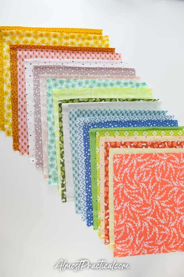 a selection of 10 inch fabric squares in fall colors and prints