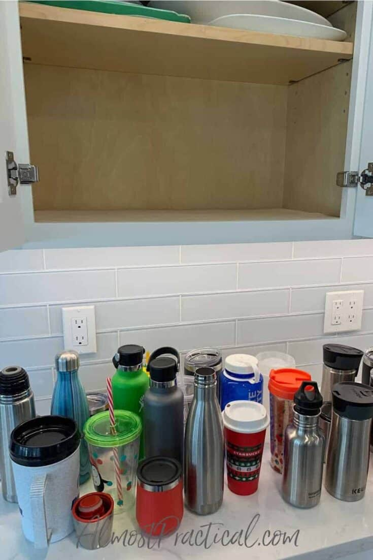 reusable water bottles on counter with empty cabinet above