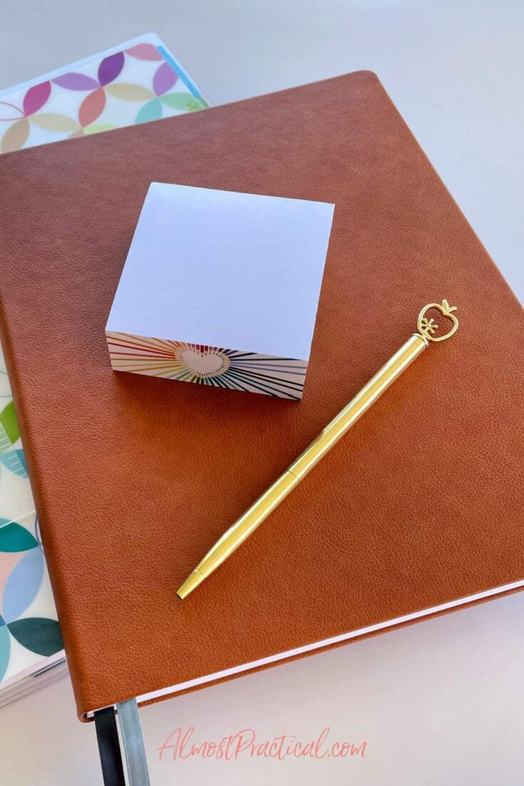 sticky note cube and gold ballpoint pen with an apple shape on top