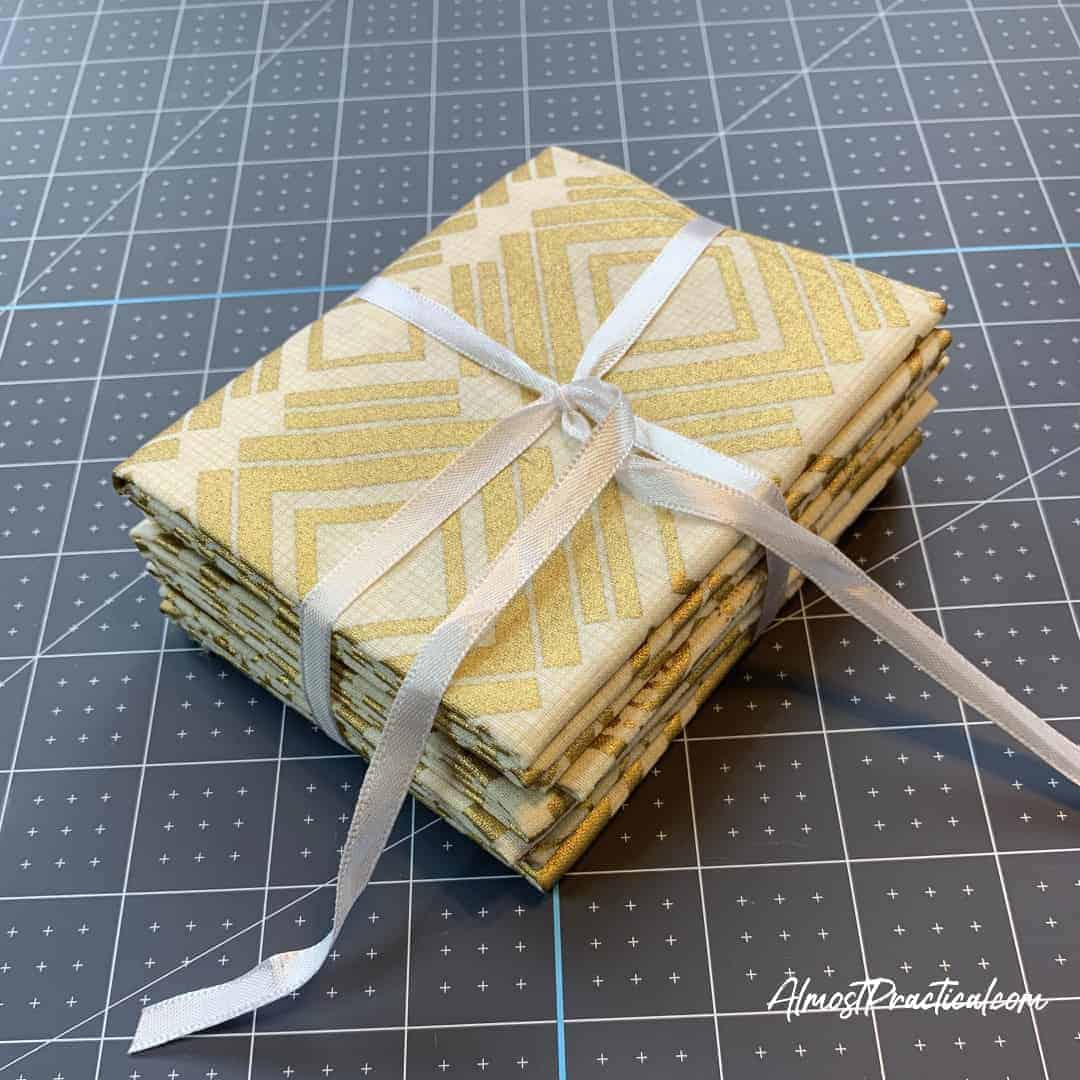 fat quarter stack of fabric in cream and gold tied with a white ribbon