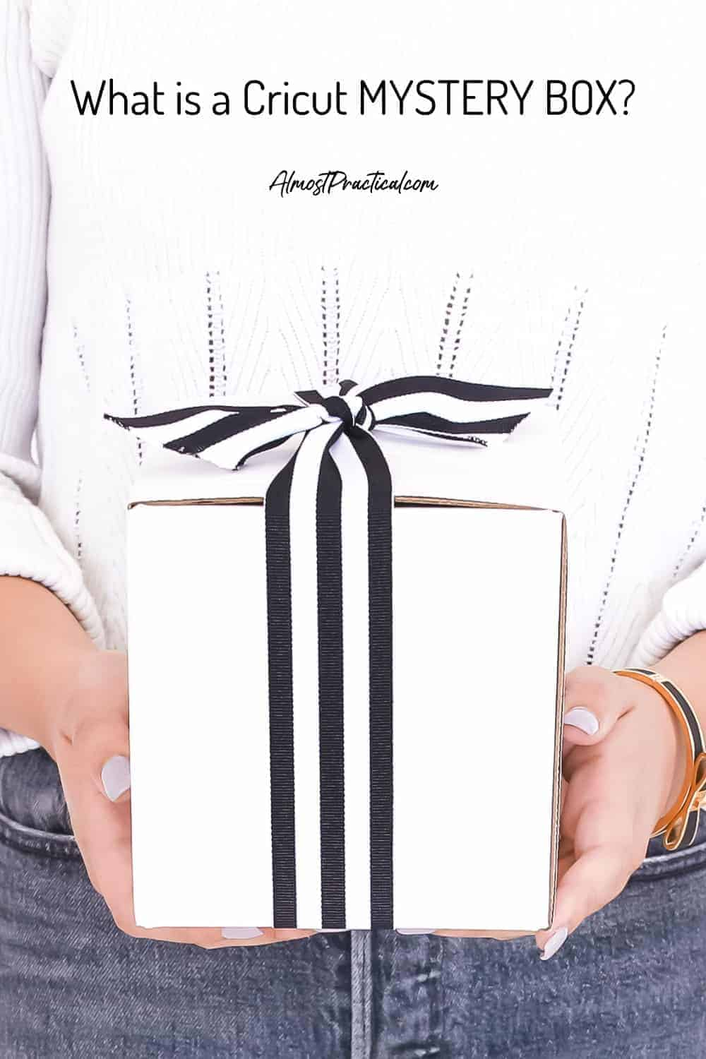 woman holding white gift box with black and white stripe ribbon